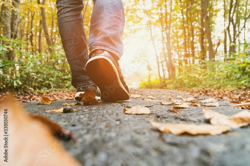 Low Section Of Man Walking On Road In Forest During Autumn - fototapety na wymiar