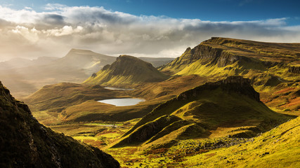 Scenic view of Quiraing mountains in Isle of Skye, Scottish highlands, United Kingdom. Sunrise time with colourful an rayini clouds in background.