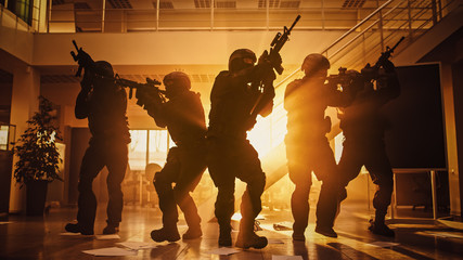Masked Fireteam of Armed SWAT Police Officers Storm a Sunny Seized Office Building with Desks and Computers. Soldiers with Rifles Move Forwards and Cover Surroundings. Shot with Yellow Warm Filter.