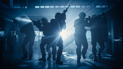 Masked Fireteam of Armed SWAT Police Officers Storm a Dark Seized Office Building with Desks and Computers. Soldiers with Rifles and Flashlights Move Forwards and Cover Surroundings.