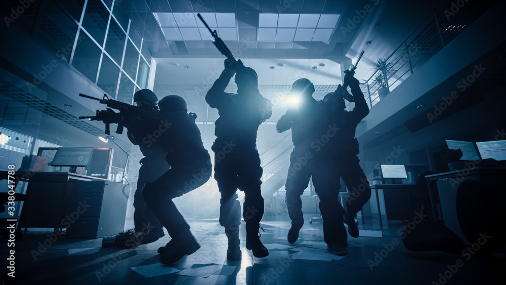 Fototapeta Masked Team of Armed SWAT Police Officers Move in a Hall of a Dark Seized Office Building with Desks and Computers. Soldiers with Rifles and Flashlights Surveil and Cover Surroundings. Low Angle Shot.