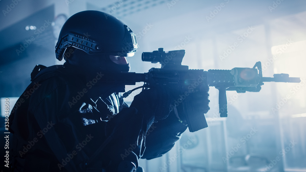 Fototapeta Close Up Portrait of Masked Squad Member of Armed SWAT Police Officers Who Storm a Dark Seized Office Building with Desks and Computers. Soldiers with Rifles and Flashlights.
