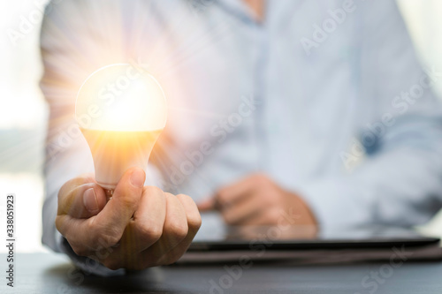 Fototapeta Businessman hands holding the light bulb that is illuminating on the table