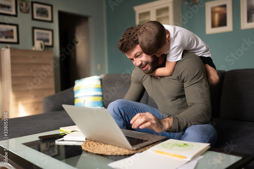 Fotografia Man working remotely and playing with son at home