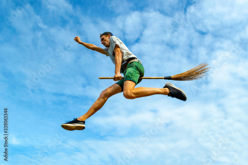 Photo Young man flying on the broom with outstretched arm in the blue sky of Siquijor