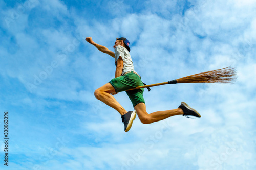 Young man outstretched arm flying on the broom in the blue sky of Siquijor Wallpaper Mural