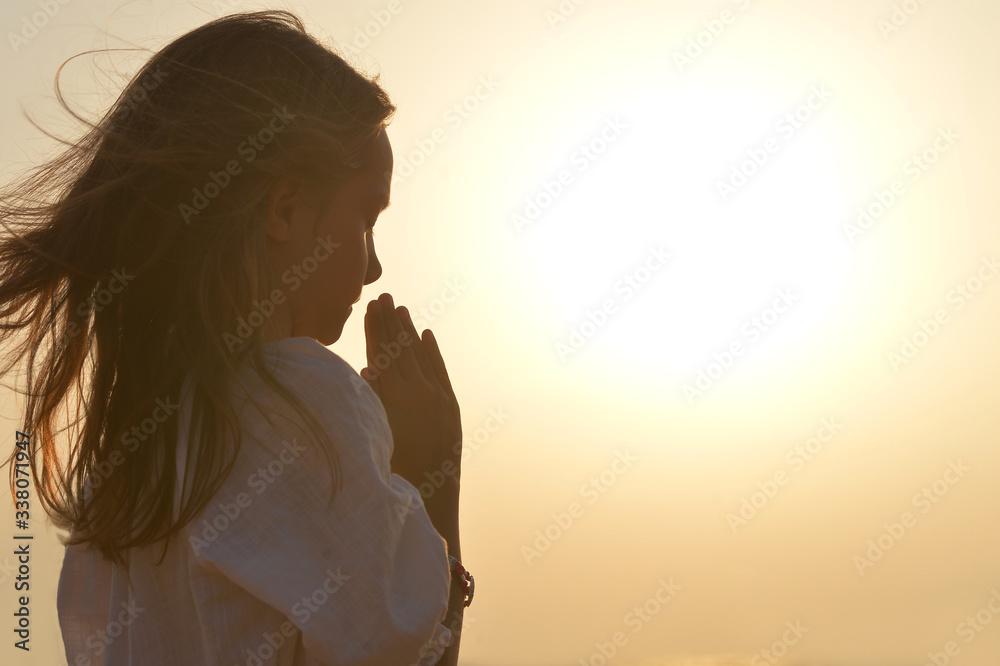 Fototapeta Portrait of little girl praying on light background