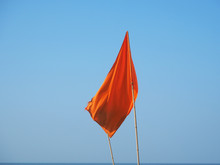 Red Warning Flag At The Beach. Sign Prohibiting Swimming In This Place