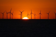 Silhouette Wind Mills On Land Against Sky During Sunset