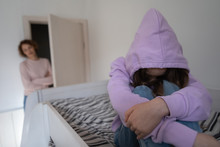 Depressed Teen Girl Wearing Hood Sitting On Bed Ignoring Mother. Sad Teenage Daughter Hiding Problem From Worried Parent Single Mom Having Psychological Trauma After Family Conflict, Divorce Concept.