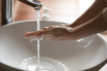 Young Woman Washing Soapy Hands With Soap Sanitizer Rinsing Under Warm Water Over Bathroom Sink To Kill Virus. Hygiene Precautions For Coronavirus Covid 19 Infection Prevention Concept. Close Up View