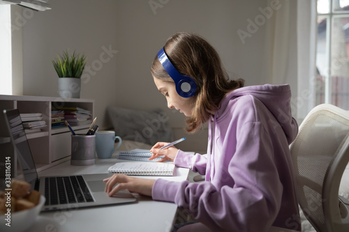 Teen girl school pupil wearing headphones studying online from home making notes. Teenage student distance learning on laptop doing homework, watching listening video lesson. Remote education concept