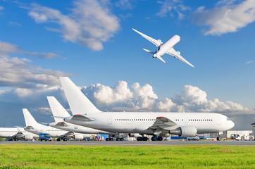 Pogled na zrakoplove koji stoje na aerodromu i zrakoplov koji polijeće na nebu.