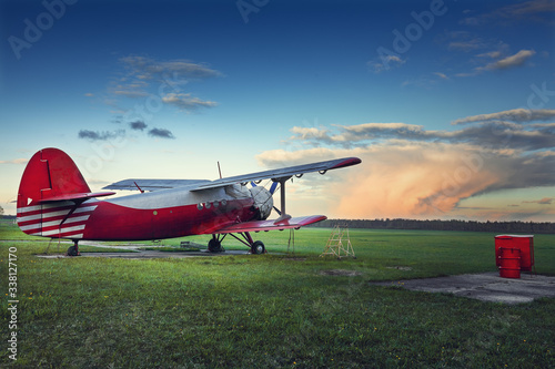 Old red biplane on a green field at sunset Wallpaper Mural