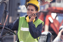 Professional Female Worker Driving Forklift Using Walkie-talkie In Shipping Yard Industrial Container Warehouse Import And Export.