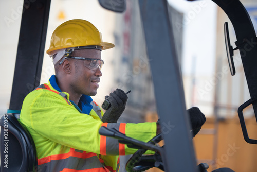 Tablou Canvas Male worker driving forklift and using walkie-talkie in shipping yard industrial container warehouse
