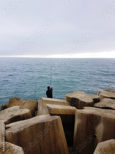 Fotografía Rear View Of Mature Man Fishing In Sea While Sitting On Rock Against Cloudy Sky