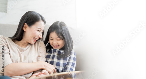 Mother and her daughter child girl playing her mom in sofa living room at home Fototapet