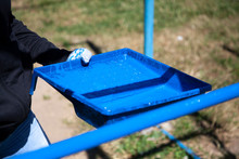 Painting The Playground. Blue Paint On The Cyst. Decoration Work. Creating A Layer Of Oil Paint On The Pipe.