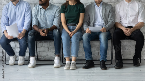 Fototapeta Close up of diverse multiracial young people sit in queue line wait for interview, concentrated multiethnic candidates applicants feel anxious before recruitment talk, employment concept obraz