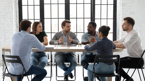Fotografía Diverse multiracial businesspeople sit at desk in office brainstorm discuss busi