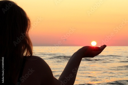 Optical Illusion Of Silhouette Woman Holding Sun While Standing At Beach During Wallpaper Mural