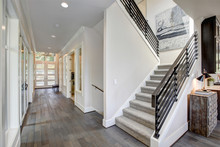 Hallway Features A Staircase With Gray Carpet Runner. Luxury American Modern Home.