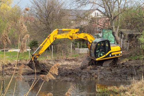 Crawler excavator or digger dredges on the lake Fototapet