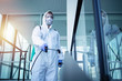 canvas print picture - Shot of male person in white chemical protection suit doing disinfection of public areas to stop spreading highly contagious corona virus. Stop coronavirus or COVID-19.
