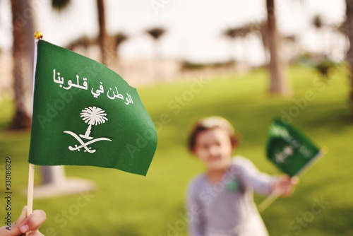 Obraz Close-up Of Person Holding Flag With Girl In Background Outdoors - fototapety do salonu