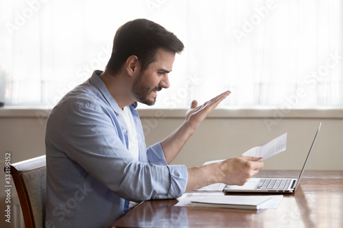 Fotografija Angry young man holding paper letter, irritated by bad news banking debt notification, sitting at table with computer at home