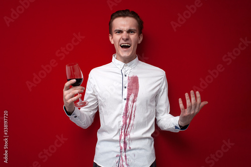 sad guy in a white shirt spilled red wine on himself on a red background, an ang Fototapet