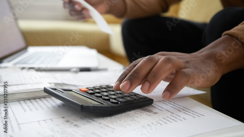 Fototapeta Close up black man hand using calculator and laptop for calculating finance. African american businessman taxing, accounting, statistics and credit analytic for mortgage payment. obraz