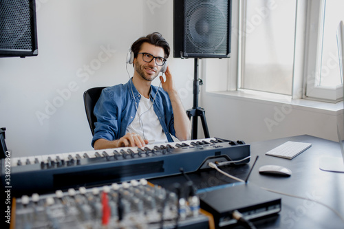 Fototapety, obrazy: Male music arranger composing song on midi piano and audio equipment in digital recording studio. Man produce electronic soundtrack or track in project at home.