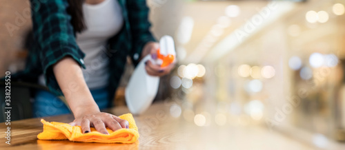 Obraz Close up view of happy woman clean home or restaurant. She wiping dust using spray and orange fabric cleaning on dirty table. House keeping maid cleaning service job to prevent covid19 virus outbreak. - fototapety do salonu
