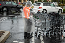 Essential Worker At Grocery Store In Rain Coat Collecting Shopping Carts In The Rain. The Image Was Taken During The Coronavirus Pandemic