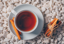 Top View A Cup Of Tea With Dry Cinnamon On White River Rocks Background. Horizontal