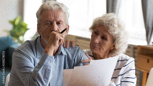 Fototapeta Unhappy older couple reading documents, checking domestic bills, caring mature wife comforting sad upset husband holding debt notification, stressed about financial problem or bankruptcy obraz