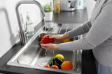 hygiene, health care and safety concept - close up of woman washing fruits and vegetables in kitchen at home