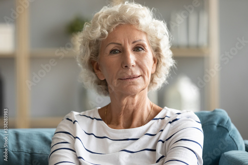 Obraz Head shot portrait close up beautiful aged mature woman with grey curly hair sitting on cozy couch, posing for photo at home, attractive older senior female looking at camera, natural old beauty - fototapety do salonu
