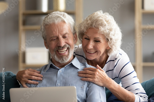 Leinwand Poster Smiling older couple looking at laptop screen together close up, mature woman an