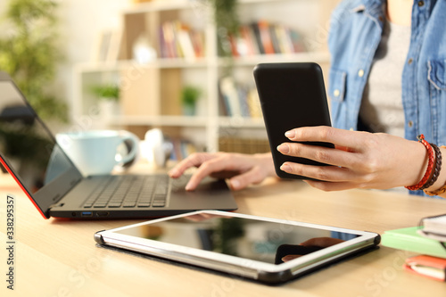 Student girl hands using multiple devices at home