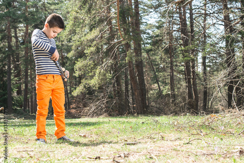 Canvas-taulu Boy Playing With Slingshot While Standing On Land In Forest