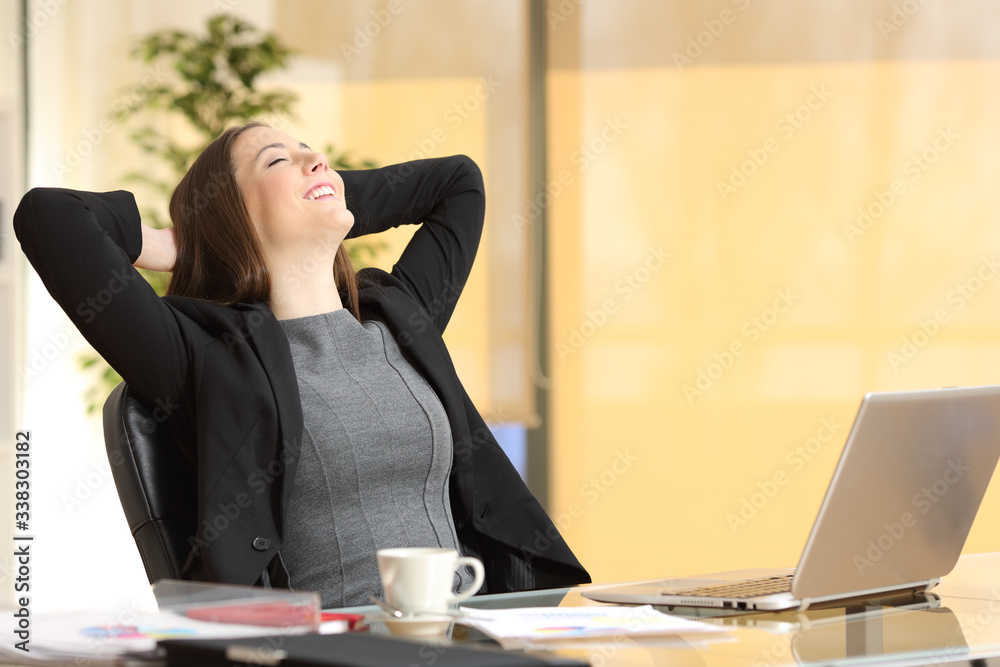 Fototapeta Happy executive woman breathing fresh air at her desk