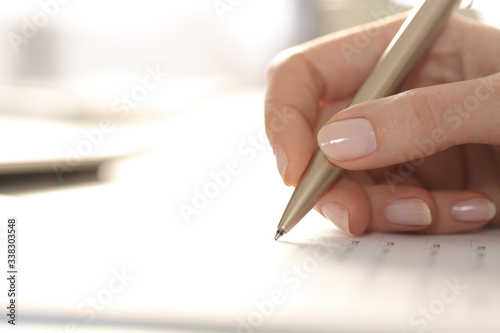 Fotomural Woman hand filling out form with pen on a desk