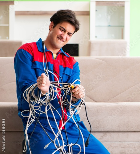 Fototapeta Electrician contractor with tangled cables