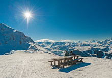 Two Skiers Sat At Picnic Table...