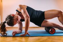 Woman Massaging Legs With Foam Roller