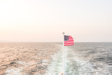 American Flag In Sea Against Clear Sky During Sunset