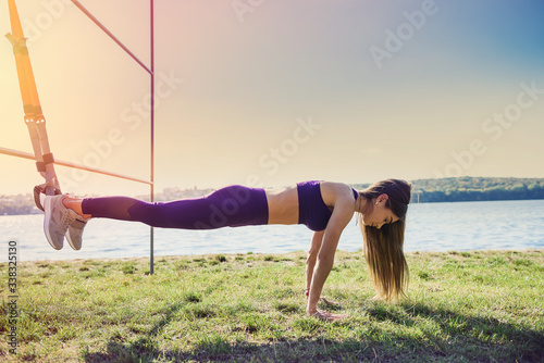 Fotografie, Tablou Young woman exercising with suspension trainer sling in park, near the lake